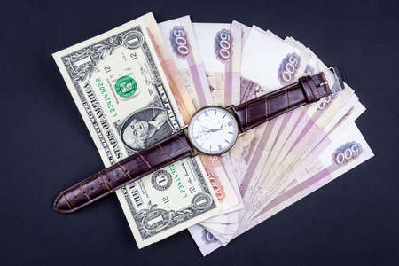 Watch and wallet with money on a black background. The concept of rejection of paper money, inflation, financial crisis.