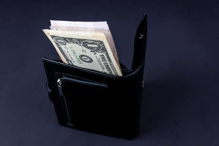 One dollar is in a black wallet on a black background
