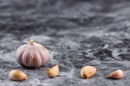 Fresh garlic on vintage table. Peeled garlic bulb and gloves on granite texture