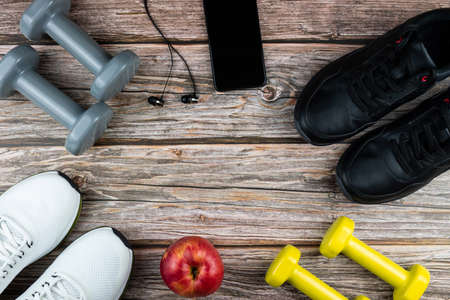 Sneakers, dumbbells, mobile phone with headphones on a wooden background. Concept of sports, fitness, healthy lifestyle. Top view. Copy space.