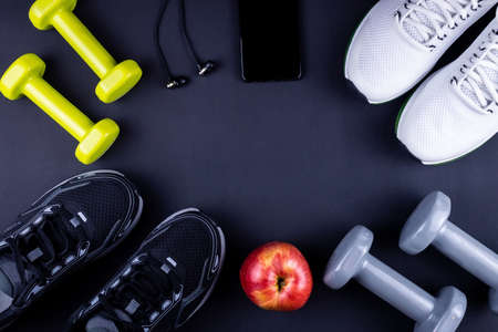 Sneakers, dumbbells, mobile phone with headphones on background of black fitness mat. Concept of sports, fitness, healthy lifestyle. Top view. Copy space.