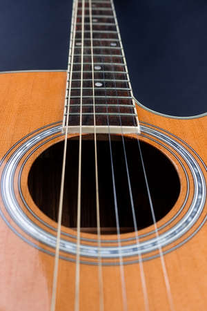 yellow guitar pick tucked into gold acoustic guitar strings on a dark wood fret board. Stock Photo