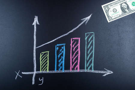 Dollar growth chart drawn on chalkboard. Investment concepts and interests Business growth. Rising graph made out of dollars. Фото со стока