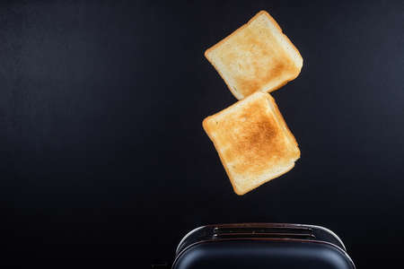 Bread coming out of the toaster with minimalist black background