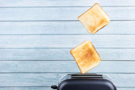 Bread coming out of the toaster with minimalist wooden background