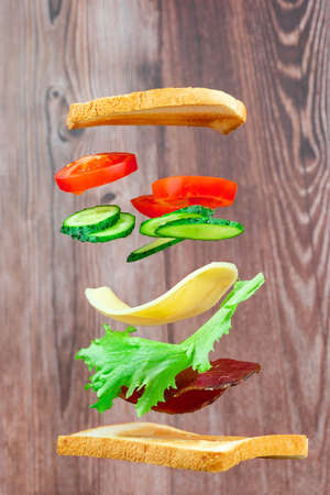 Flying layers of sandwich with ham, cheese, and vegetables on the wooden background. Breakfast food concept Stock Photo