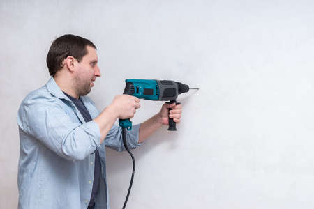 smiling handsome young male construction worker repairman with puncher on white background