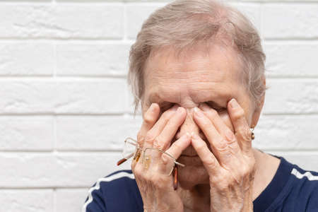 Close up of unhealthy elderly woman take off glasses massage eyes suffering from strong migraine or headache, unwell sick senior female grandmother struggle with blurry vision or dizziness at home