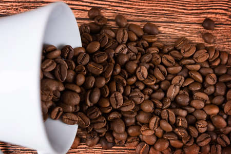 a cup of coffee and coffee beans in a bag on a dark background, top view 版權商用圖片