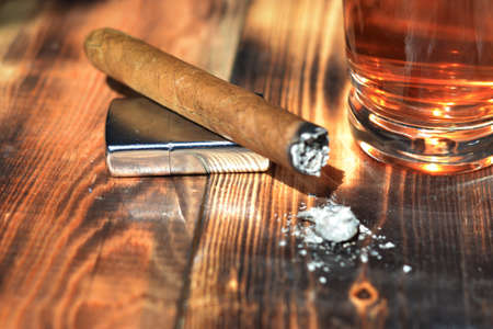 Cigarette lighter and cognac on the table Stock Photo