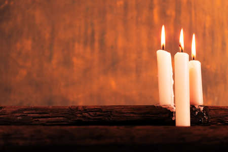 Candle on a old oak wooden table. Beautiful gold background.Religion concept. Foto de archivo