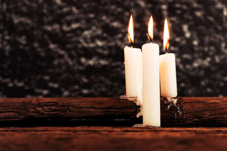 Candle on a old oak wooden table. Beautiful gold background.Religion concept. Stock Photo