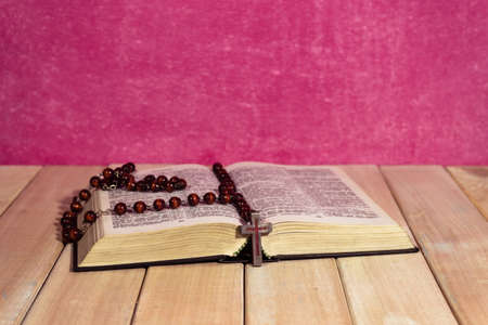 Bible on a new wooden table. Beautiful pink background.Religion concept.