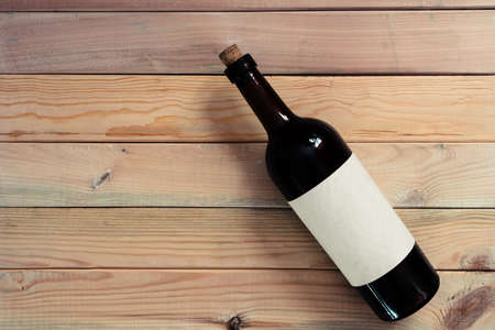 Black bottle of red wine on a red and new wooden table. Beautiful background Banque d'images