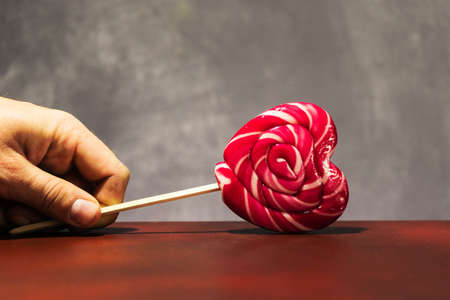 Heart shaped lollipop on a wooden table