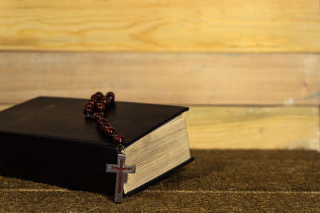 Bible and the crucifix on a gold table. Beautiful new wood background. Religion concept