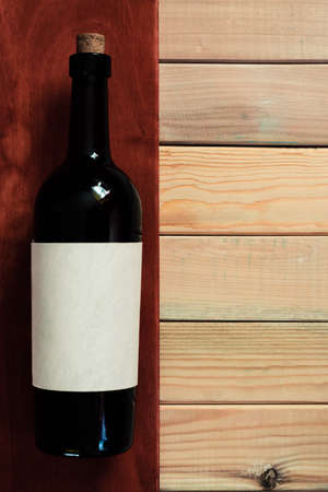 Black bottle of red wine on a red and new wooden table. Beautiful background 写真素材