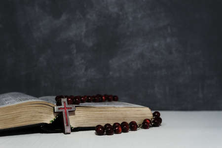 Bible and the crucifix on a new wooden table. Beautiful DARK background. Religion concept Foto de archivo