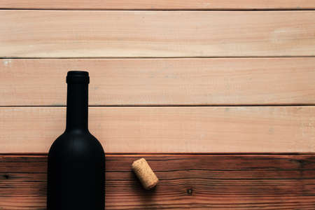 Black bottle of red wine on a wooden table. Beautiful new wooden background