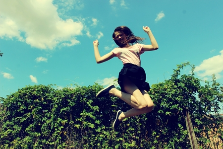 human energy: Jumping girl in nature in the summer.