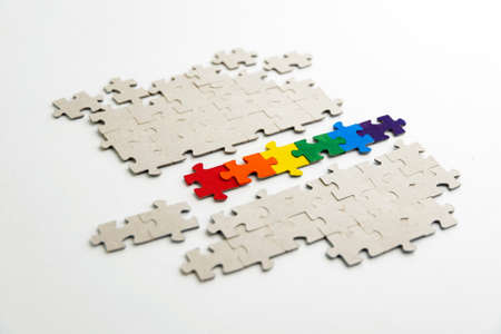 LGBT pride flag, built from a puzzle, among gray puzzles, short focus, on a white background, side view