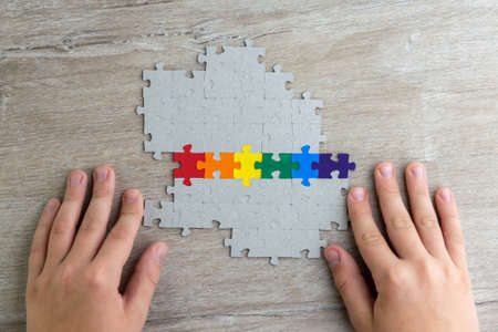education in the spirit of equality and tolerance: a student builds a LGBT pride flag of the puzzle, short focus, top view