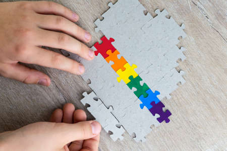 sex education in the spirit of equality and tolerance: a student builds a LGBT pride flag of the puzzle, short focus, top view Banco de Imagens
