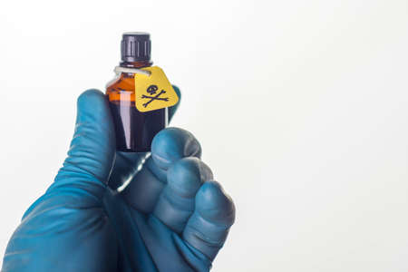 dark jar, etiquette with a warning sign about the content of poisonous substances, in the hand of a medic