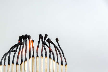row of wooden matches glows, several embers are smoldering, small flames
