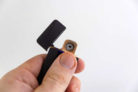 electronic lighter in man's hand, matte surface, gold frame, short focus, on a white background