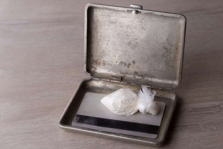 dose of cocaine in a plastic bag and a card inside an open cigarette case, on a dark background, reduced contrast