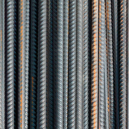 rough iron grunge background: glittering new clean reinforcement bars, short focus