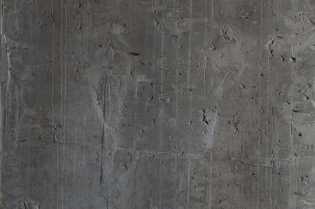 grunge background: rough concrete wall with cracks and dents, traces of formwork