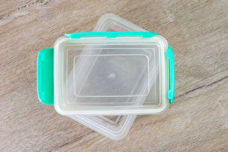 eco-friendly transparent plastic food storage container, color lid, on a wooden table, close, short focus Stockfoto