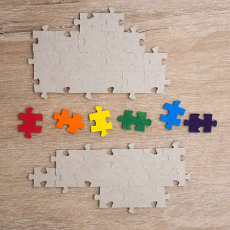 equality concept: LGBT pride flag built from a puzzle, among gray puzzles short focus, top view Banco de Imagens