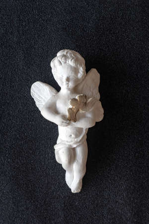 Valentine's Day, Christmas: Antique statuette of a white angel with a cross in hand, on black