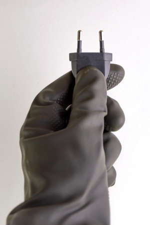 concept of energy dependence: a plug and cable in the person's hand, a black protective glove