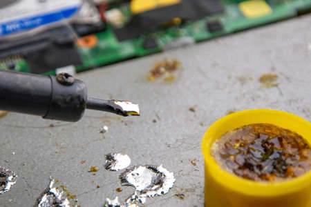hot smoking soldering iron with rosin and tin, molten metal drops, electronic devices in the background, selective focus, close Stock fotó