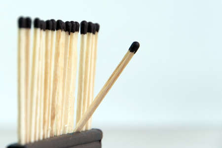 rebel: a row of wooden matches ready to burn together, one match leaves row Stock Photo