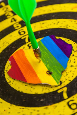 Concept - harassment of LGBT community freedom: burnt and torn rainbow heart pierced with darts, short focus