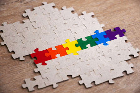 equality concept: LGBT pride flag, built from a puzzle, among gray puzzles, short focus, side view