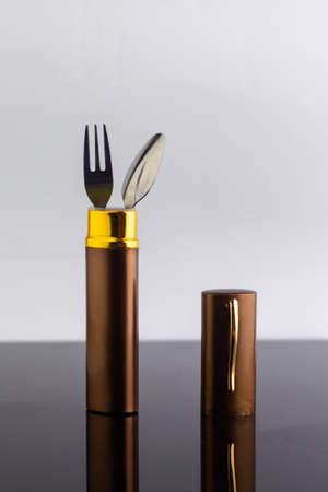 set of dining items for camping: small spoon and fork, storage case, dark background