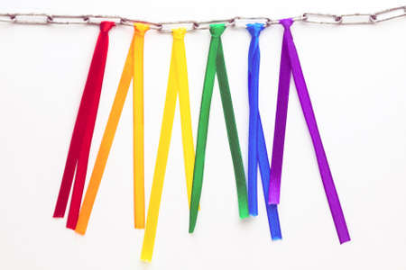 LGBT pride flag, built of colored ribbons tied on an iron chain, short focus, on a white background