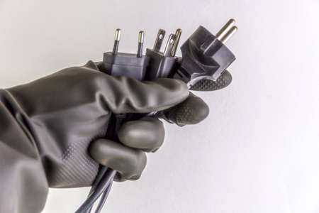 concept of energy dependence: several different plugs and cables in the person's hand, black protective glove Stock Photo
