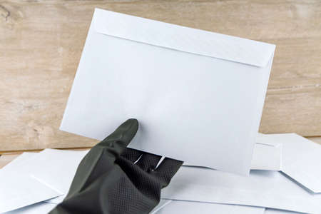 man with protective gloves examines anonymous envelopes