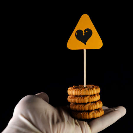 sweets harm concept: Sign of danger of heart attack over cookies