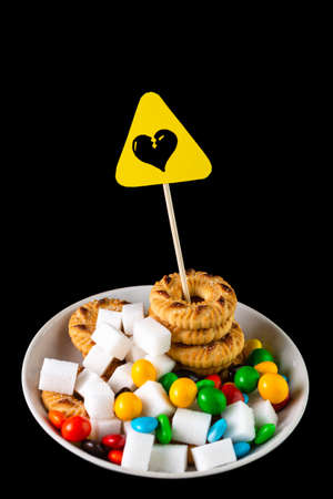 sweets harm concept: Sign of danger of heart attack over sugar, cookies and chocolate candies Banque d'images