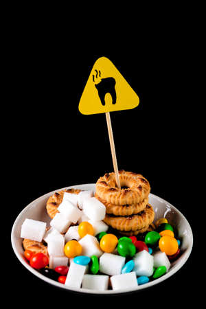dental health concept: caries danger sign standing over a plate with cookies, sugar and sweets