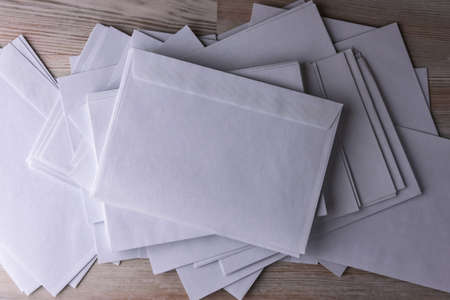 Outgoing correspondence: few empty white envelopes on a wooden desk in the office, enhanced contrast
