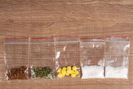 death row concept: tobacco, weed, MDMA tablets, amphetamine crystals, heroin in plastic bags, on a light background. Enhanced contrast, partial blur.